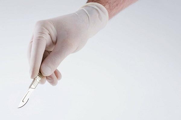 Скальпель в руке хирурга